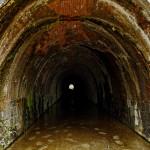 水の溜まった洞口をのぞくと反対側の光が小さく見える。